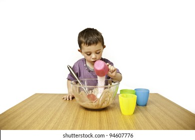 PIcture of a happy young toddler mixing ingredients into a bowl isolated on a white background
