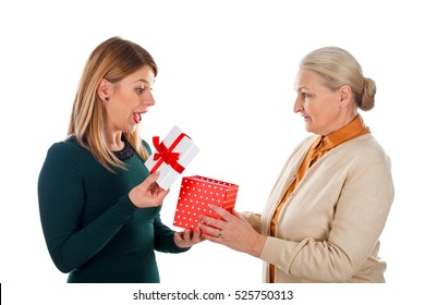 Picture of a happy young woman receiving a Christmas gift from her mother