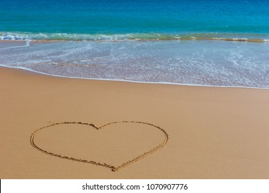 Picture of the heart on wet beach sand with the turquoise sea on background.