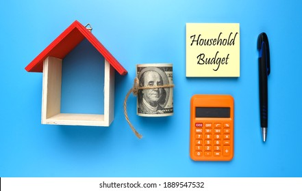 A picture house miniature, with fake money, notepad written household budget, calculator and pen on blue background