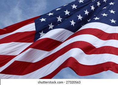 Picture of a huge American Flag waving in the breeze on a sunny day.