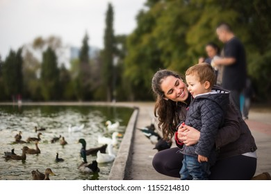 Picture of hugging aunt mother and son in a lake with ducks.