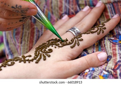 Picture of human hand being decorated with henna tattoo