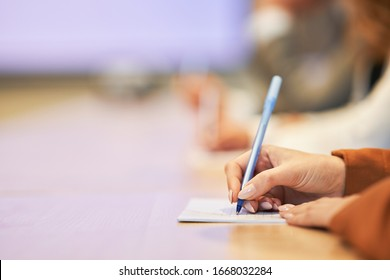 Picture of a human hand writing something on the paper on the foreground