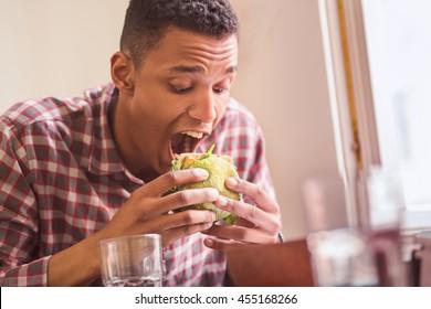 Picture of hungry man eating vegan burger in vegan restaurant or cafe. Handsome man following vegan diet.