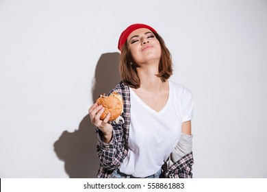 Picture of hungry young woman dressed in shirt in a cage print wearing hat standing isolated over white background and eating burger