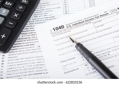 Picture of income tax form with calculator and pen. tax return concept