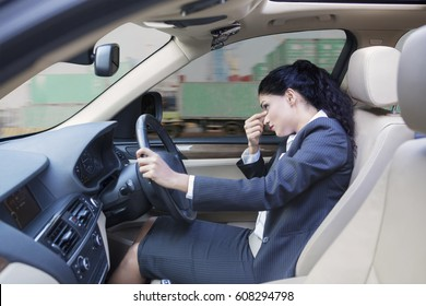 Picture of Indian businesswoman looks dizzy, driving a car while massaging her forehead