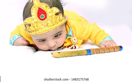 Picture of Indian Little child wearing Lord Krishna costume and celebrating Janmashtami festival. Isolated white background.
