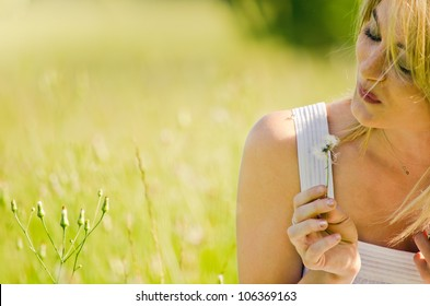 Picture of Innocence -Young girl blowing on a dandelion to make a wish.