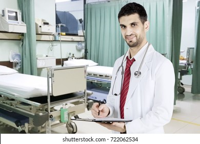 Picture of Italian man doctor smiling at the camera in the patient room while writing on the clipboard