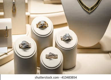 Picture of a jewelry store beige window display stands with gold diamond rings, necklaces, and earrings.