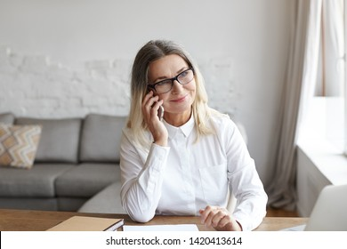 Picture of joyful positive senior woman psychologist wearing white shirt and eyeglasses sitting at desk by the window and smiling joyfully while having phone conversation, speaking to her client