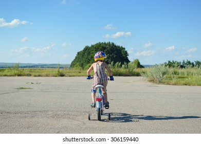 Picture of kid in a helmet riding bike on summer blue sky outdoors background