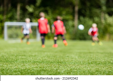Picture of kids soccer training match with shallow depth of field. Focus on foreground.