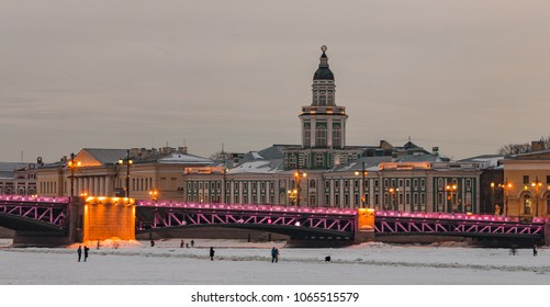 A picture of the Kunstkamera (Russia's first museum), seen behind the lit bridge at sunset.