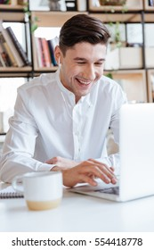 Picture of laughing man dressed in white shirt using laptop computer. Coworking. Look at laptop.