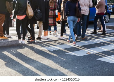 picture of the legs of a crowd of people crossing a street at the pedestrian crossing