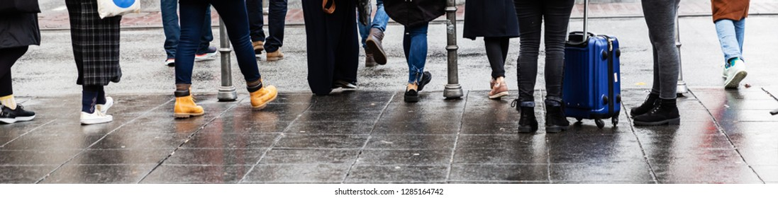 picture of legs of a crowd of people who stand at the pedestrian crossing
