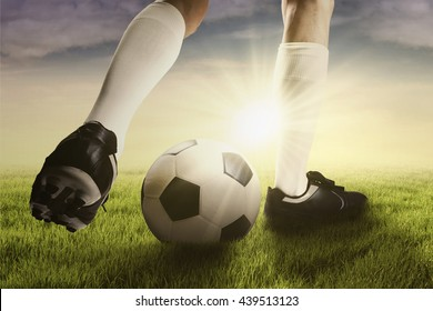 Picture of legs of soccer player doing exercise with a ball on the meadow in the morning