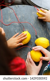 Picture of lemons with red wires on a black wooden table