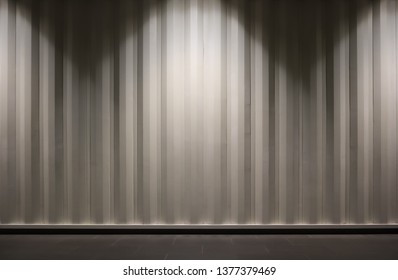 The picture of light beige container wall. Brightening by light bulb from top. Background container wall photo with copy space use as wallpaper, commercial advertise, banner and backdrop.