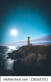 Picture of a Light house shining a light over in the darkest of nights.