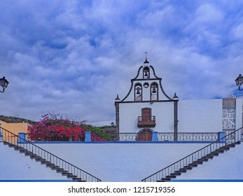 A picture like a gentle painting in white and delicate blue. A small church on a plateau with three bell giblets in white with a small balcony at the front. Right and left stairs are acute-angled.