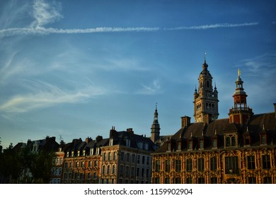 """Picture of Lille's """"grand place"""" in France, taken at sunset with few clouds."""