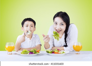 Picture of a little Asian boy and his mother eating fresh vegetables salad and drink orange juice