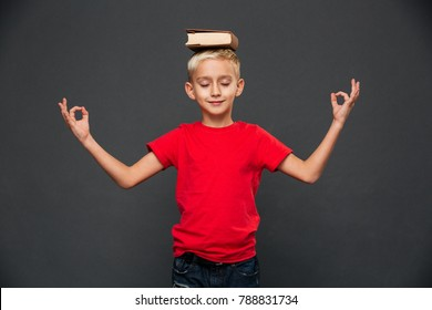 Picture of little boy child meditate isolated over grey background with book on head.