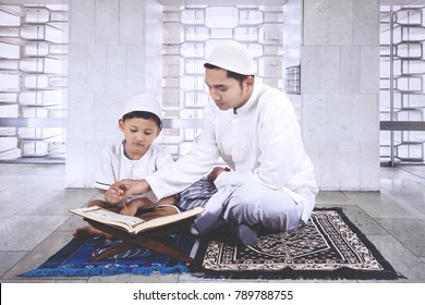 Picture of little boy learning to read the Quran with his father while sitting in the mosque