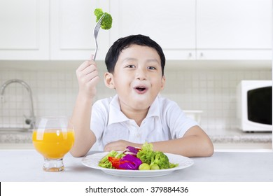 Picture of a little boy sitting in the kitchen and eats vegetable salad with orange juice