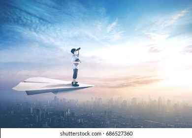 Picture of little boy standing on a paper plane while flying above city and looking with binoculars