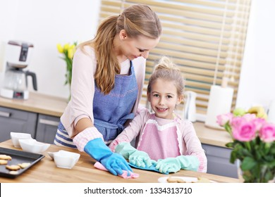 Picture of little girl and her mom in aprons having fun cleaning kitchen