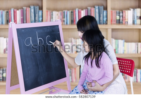 Picture of little girl learns alphabet with her teacher writing the letter on chalkboard, shot in the library
