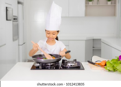 Picture of little girl wearing apron and hat while cooking healthy meal in the kitchen
