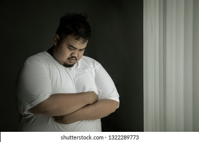 Picture of lonely obese man looks sad while standing near the window. Shot at home
