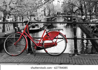 A picture of a lonely red bike on the bridge over the channel in Amsterdam. The background is black and white.