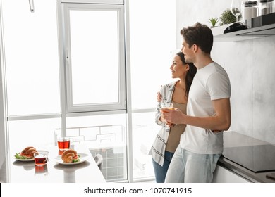 Picture of lovely couple smiling, and looking through big window while having breakfast in modern apartment in morning