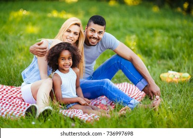 Picture of lovely couple with their daughter having picnic