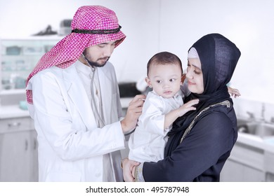 Picture of a male Arabian doctor examining a baby boy with a stethoscope in the clinic room