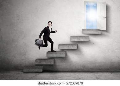 Picture of a male Asian worker walking on the stairs leads an opportunity door to success with bright sunlight