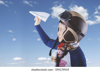 Picture of a male child holding a paper plane while wearing helmet and scarf under clear sky