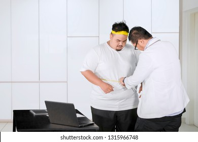 Picture of a male doctor examining fat belly of his patient by using measuring tape. Shot at the clinic
