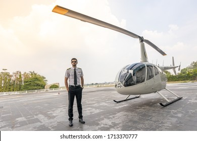 Picture of a male helicopter pilot in his white shirt with tie uniform. He is prepared for his flight. He stands in front of a white helicopter in the open area prepare to take off