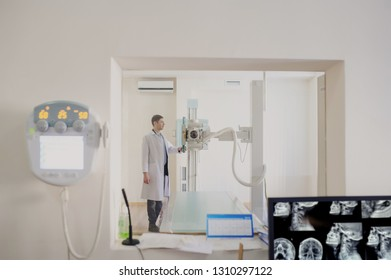 the picture of a male radiologist adjusting the X-ray machine behind the screen