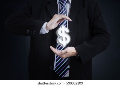 Picture of a male worker hands holding a dollar currency symbol and wearing formal suit