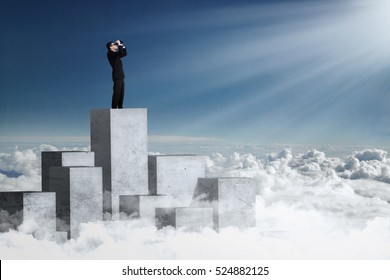 Picture of a male worker standing on the concrete wall and looking at the bright sunlight using binoculars