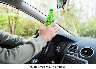 In the picture a man drinking alcohol in the car.